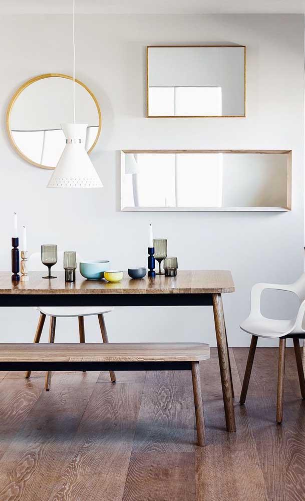 Formas geométricas puras e cruas tomam conta da parede dessa sala de jantar por meio dos espelhos