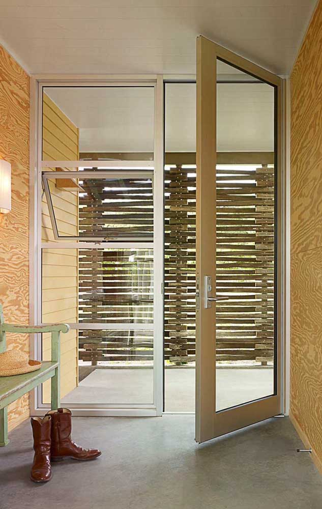 Porta e vão lateral com vitrô modelo maxim ares; a esquadria de alumínio em tom natural acompanha todo o projeto