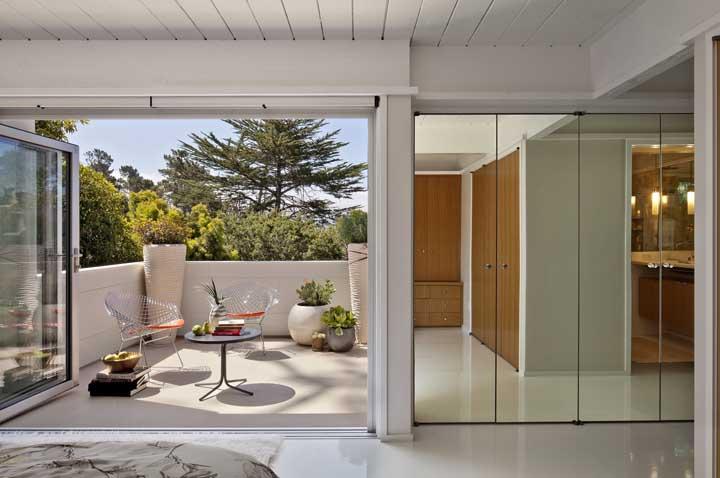 Entre a varanda e a sala de estar uma porta estilo sanfonada de alumínio