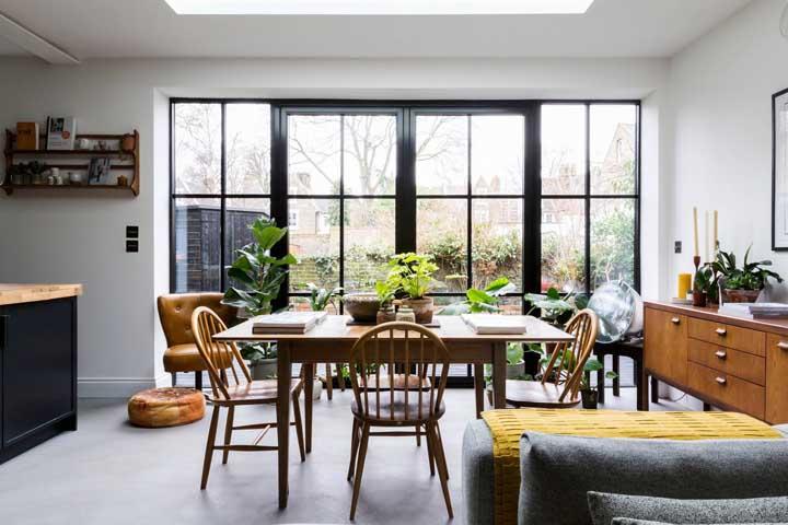 O ambiente ganhou em modernidade e sofisticação com a porta de abrir e os vãos laterais feitos em esquadria de alumínio preto