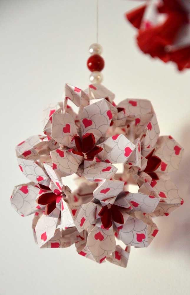Kusudama pequeno feito com papel estampado de corações; destaque para o cordão de pendurar com contas nas mesmas cores