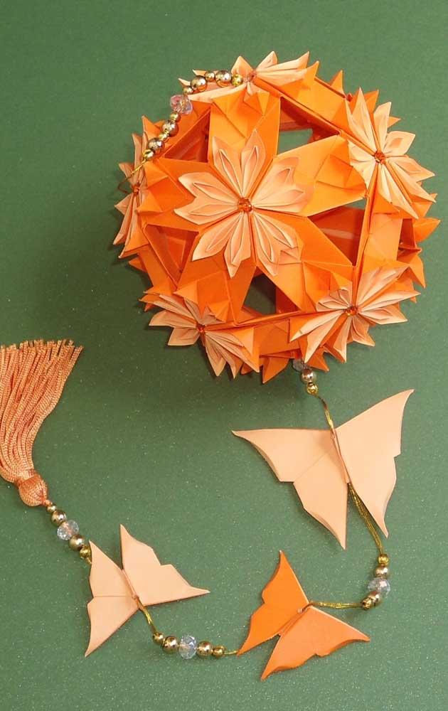 Kusudama laranja com detalhes diferenciados nas dobras e origamis de borboleta no cordão de pendurar