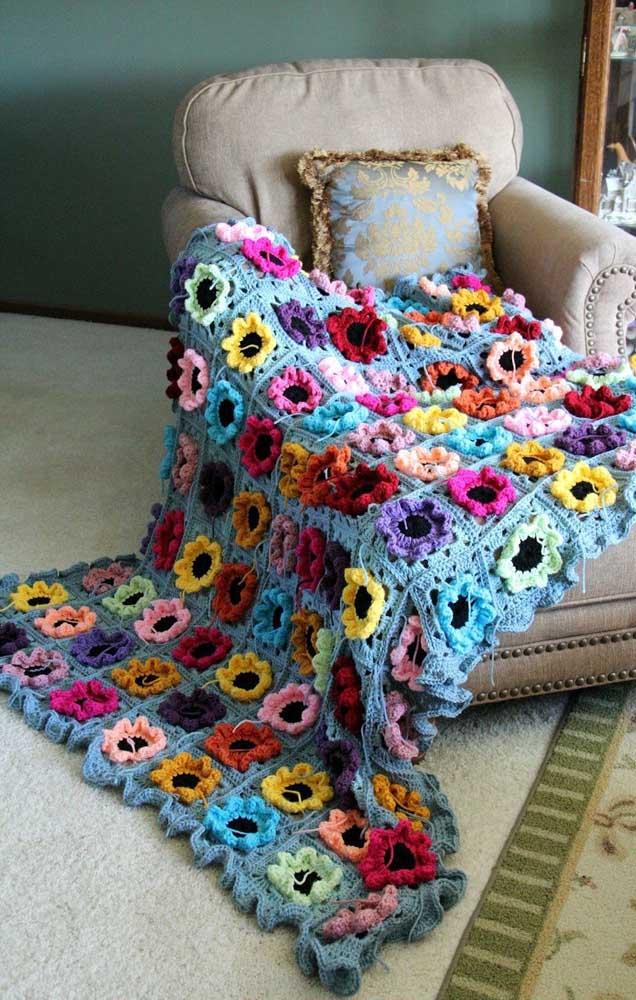 Squares de crochê com flores no meio foram unidos um a um até se tornarem um tapete em tamanho grande