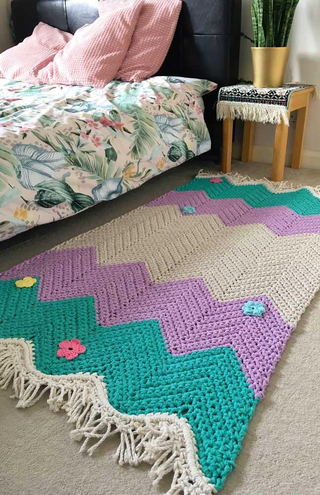Tapete de crochê retangular com flores para ser usado ao lado da cama do casal; repare que as flores foram aplicadas depois do tapete pronto