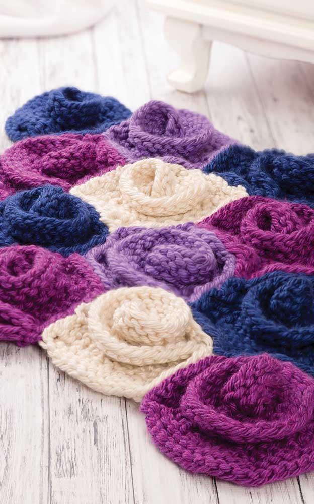 Quanta maciez, conforto e carinho você consegue enxergar nesse modelo de tapete de crochê com flores coloridas?