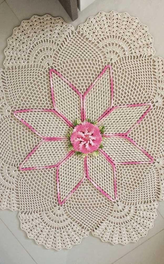 Tapete de crochê redondo com flores; note que aqui há uma flor produzida junto com o tapete e outra que foi aplicada depois como acabamento
