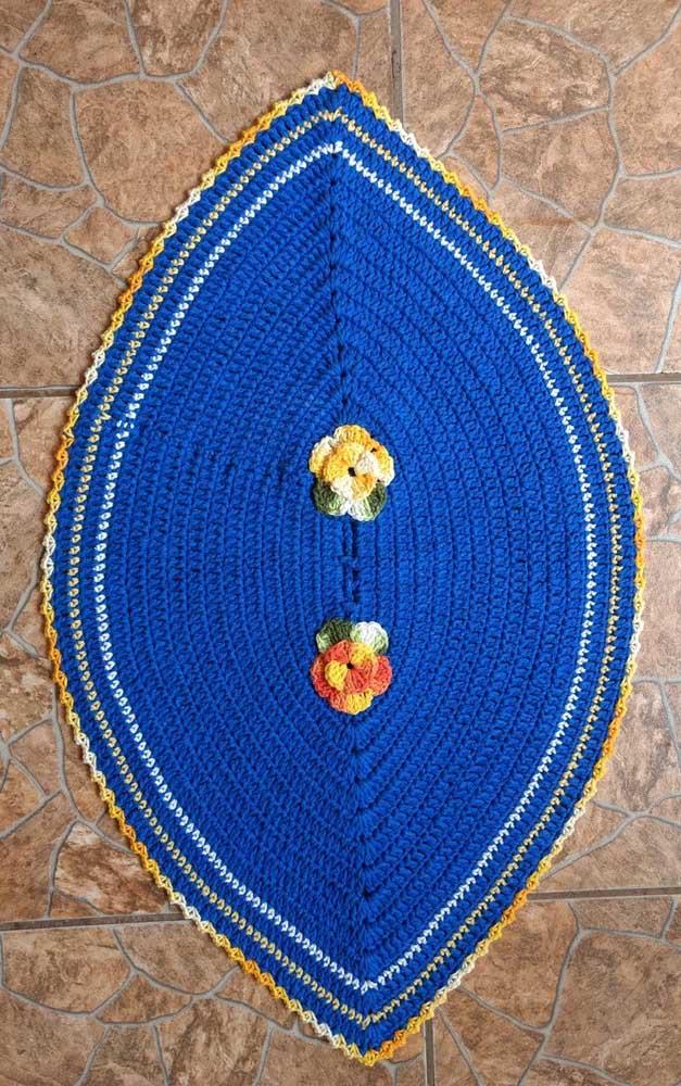 Que graça esse tapete de crochê azul em formato de folha com aplicação de flor no centro