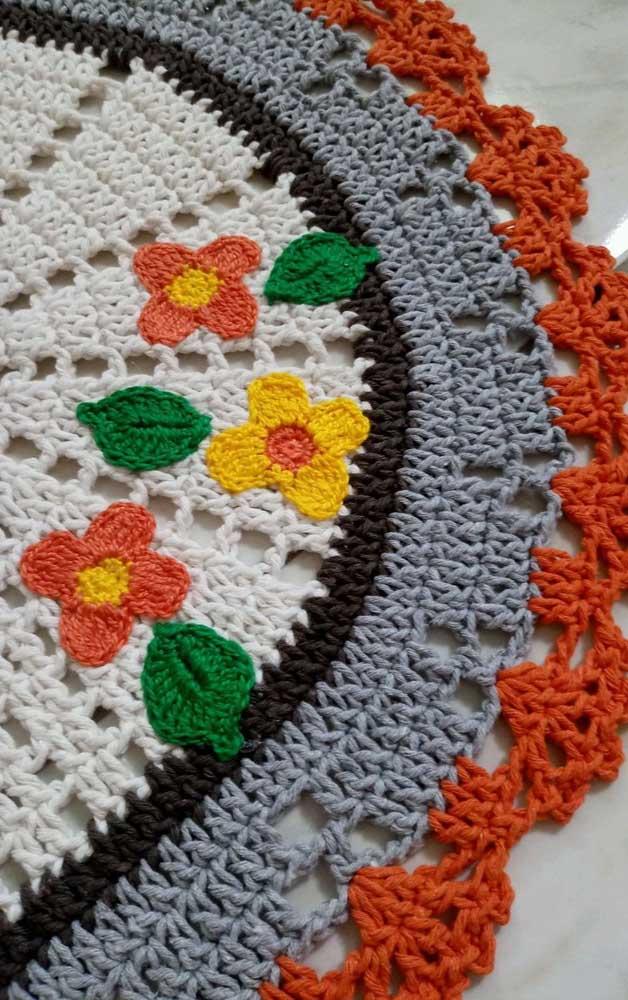 Pequenas e delicadas flores aplicadas no centro do tapete de crochê