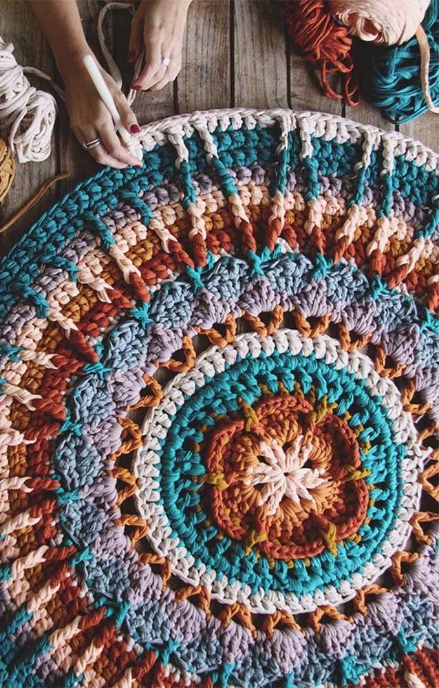 Que tal um tapete de crochê redondo com flores em estilo mais rústico feito com linhas coloridas de malha?