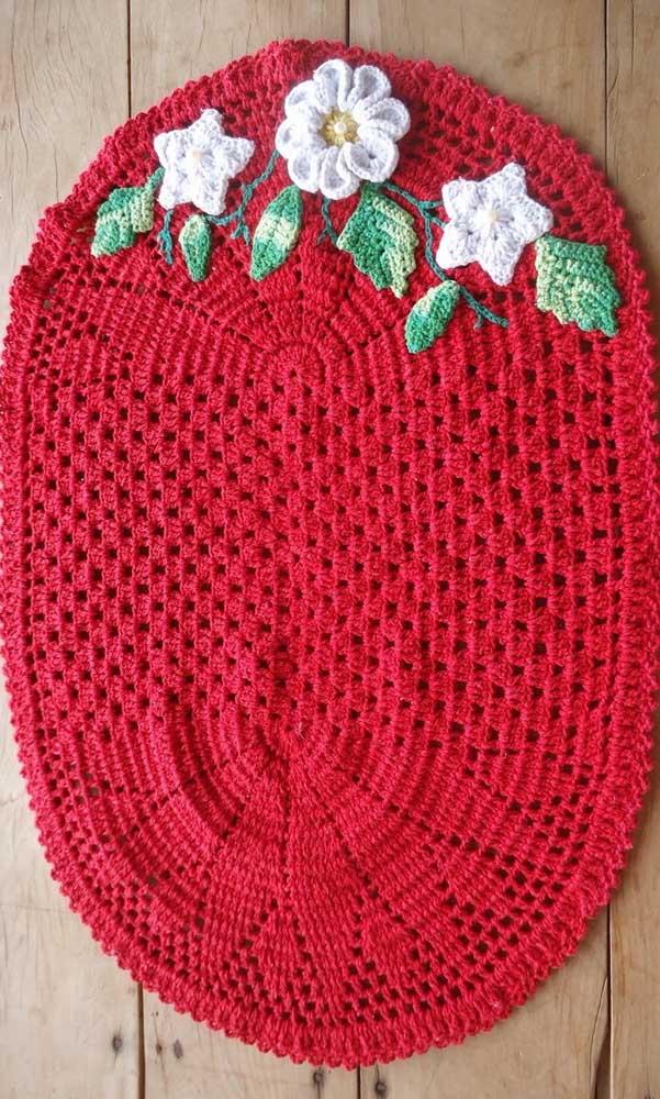 Um tapete de crochê vermelho com flores brancas para chamar de seu