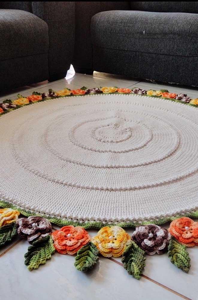 Para essa sala de estar foi escolhido um tapete de crochê redondo em barbante cru com barrado de flores