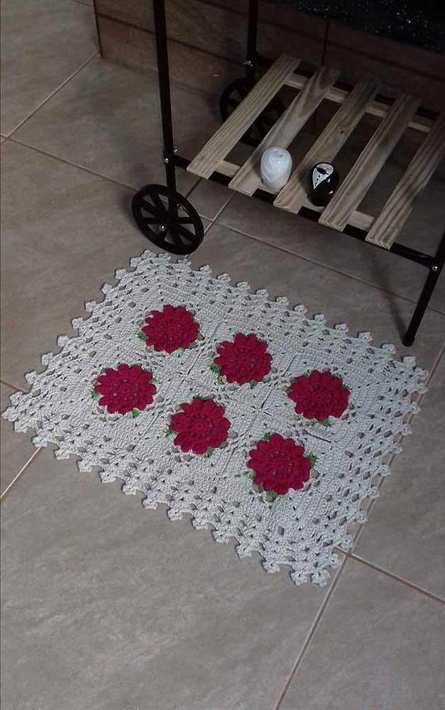 As flores vermelhas se destacam sobre o tapete de crochê em tom cru