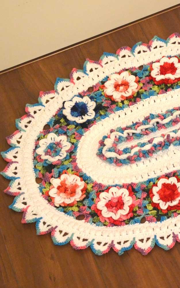 Um colorido alegre e vibrante nesse tapete de crochê oval com flores no meio
