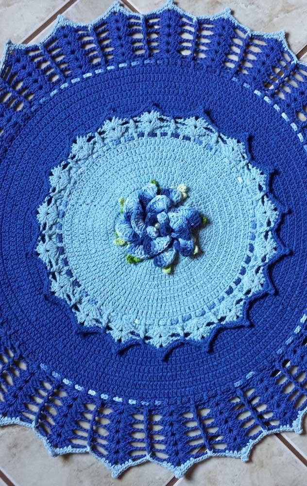 Um lindo e pacifico tapete azul de crochê com flores no centro