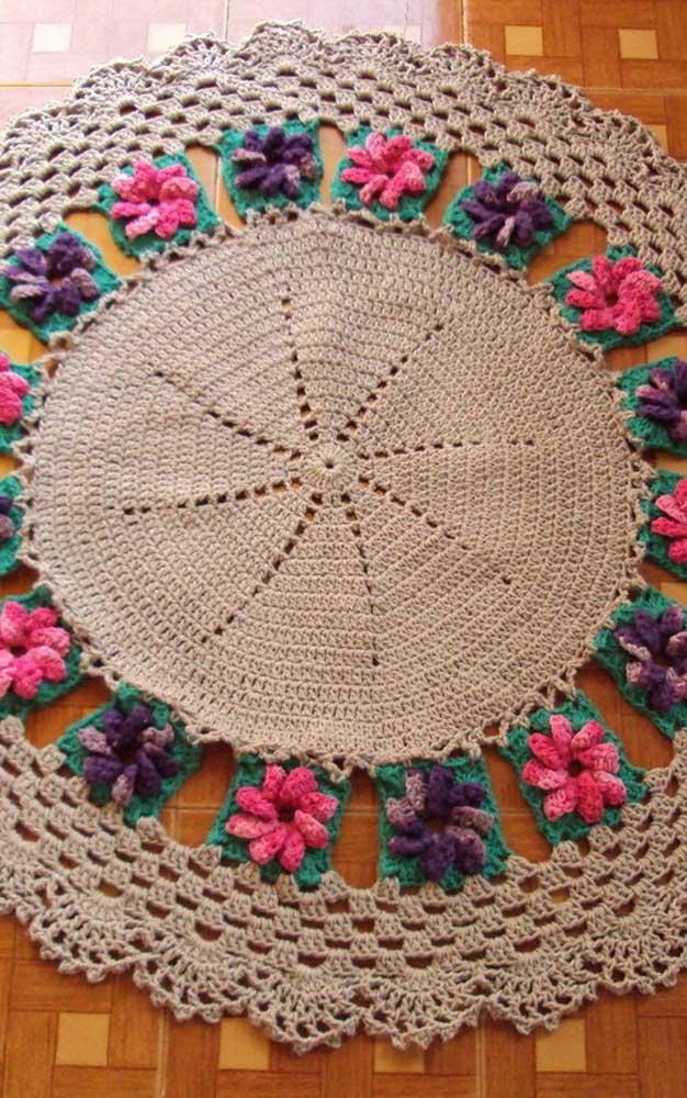 Squares com flores fazem a junção entre a parte central e a borda do tapete de crochê
