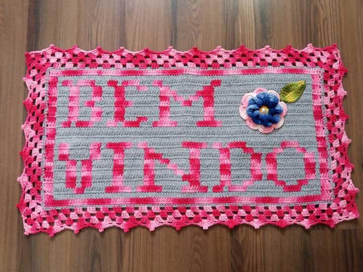 """Um tapete de crochê com a frase """"Bem Vindo"""" e uma flor, também em crochê, para completar a intenção"""