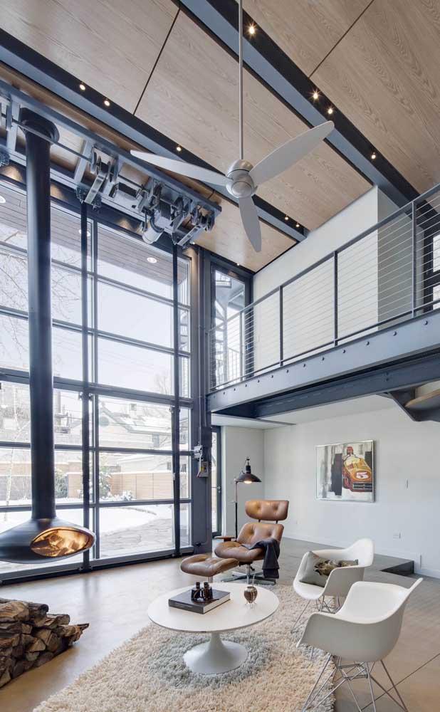 Mesmo ampla e com pé direito alto, essa sala de estar investiu em um ventilador de teto pequeno