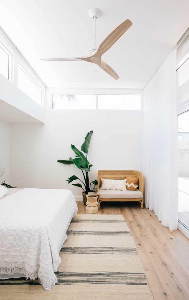 O quarto clean apostou em um ventilador de teto branco com detalhes em madeira clara