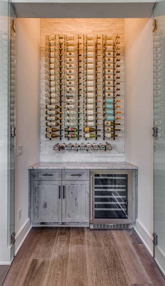 Aquele espaço da casa sem uso pode se transformar em uma linda adega; repare que aqui, a adega ganhou uma porta de vidro
