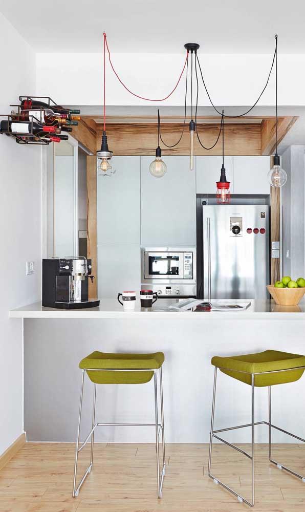 Essa cozinha americana trouxe uma mini adega de parede bem no alto, acima da linha das luminárias do balcão