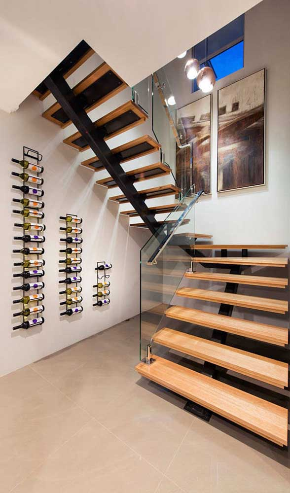 Suportes de ferro formam essa adega de parede instalada no espaço vazio embaixo da escada