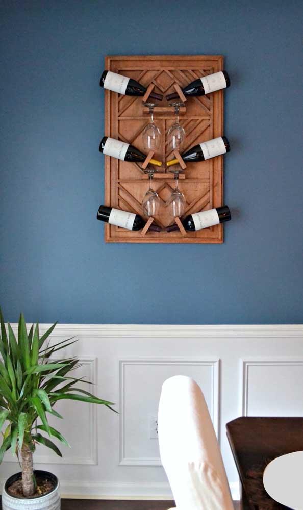 A clássica parede com boiserie recebeu muito bem a pequena adega rústica de madeira