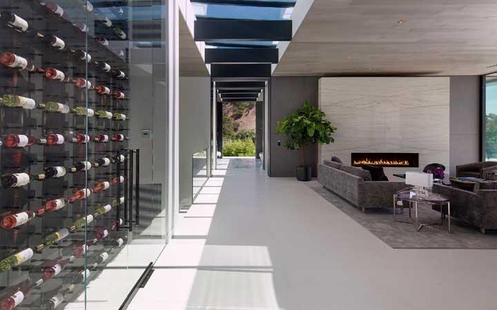A casa ampla e espaçosa conta com uma adega de parede grande e fechada por uma porta de vidro