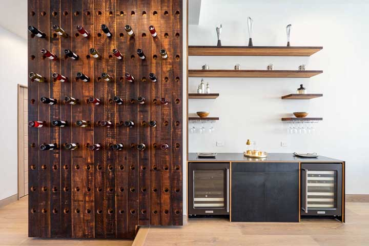 Rústica, essa adega de parede em madeira traz um encaixe diferenciado para as garrafas