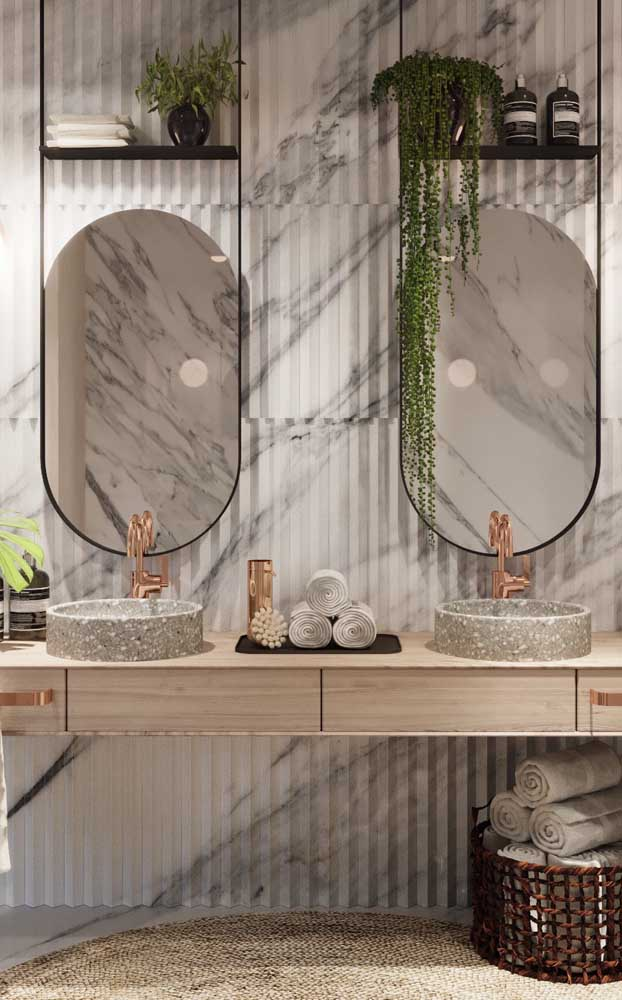 A dupla de espelhos fumê ganhou molduras minimalistas que funcionam também como suporte para as plantas