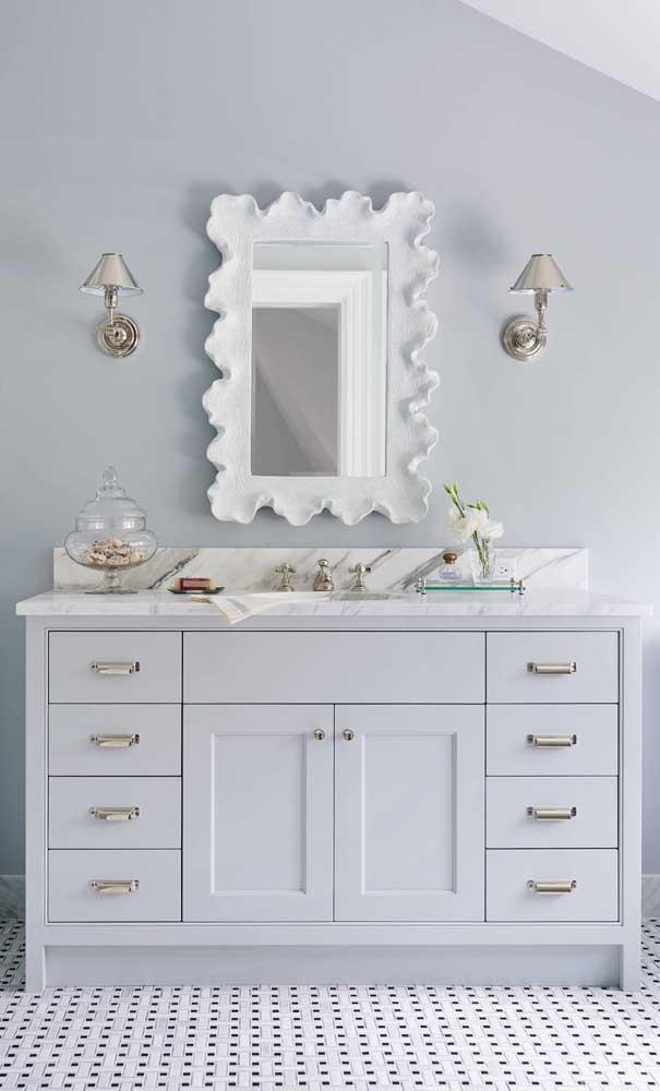 Esse banheiro de estilo clássico apostou em uma moldura de gesso para o espelho