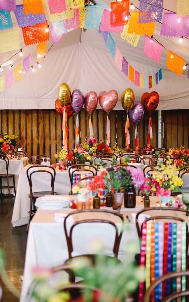 O aniversário com tema junino ficou completo com o varal de bandeirinhas coloridas; repare que o formato quadrado não tirou a graça da decoração