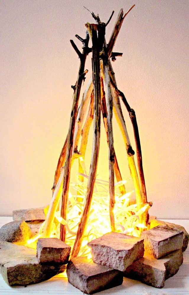 Estrutura de uma fogueira de verdade, só que ao invés do fogo foi usado um varal de lâmpadas