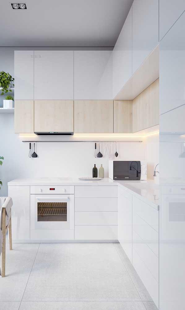 Cozinha compacta branca iluminada por fitas de led abaixo dos armários