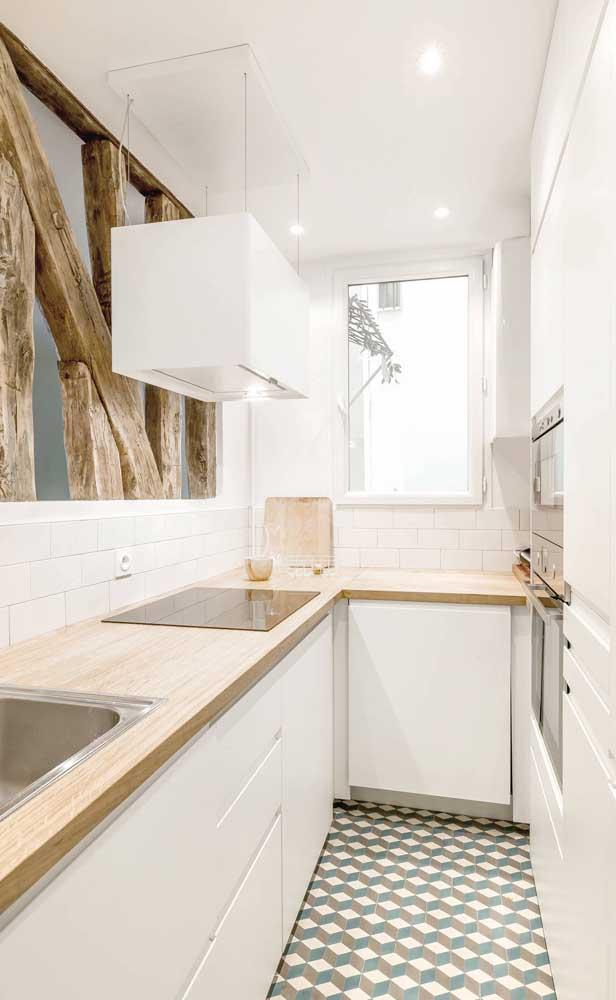 Cozinha compacta branca e com detalhes em madeira clara; a combinação de cores reforça a iluminação natural que vem da janela