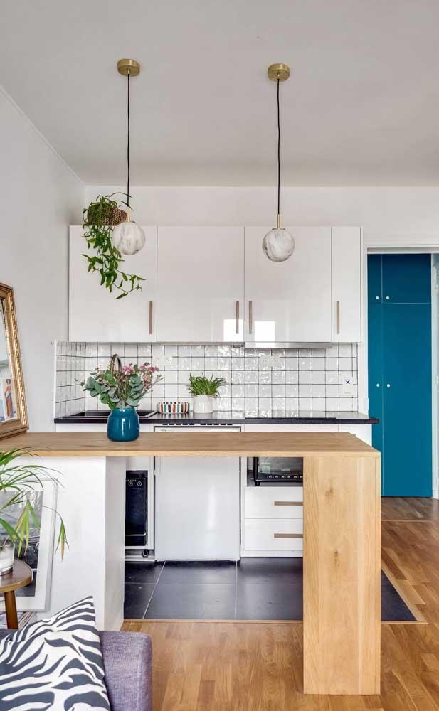 Cozinha compacta branca de apartamento; repare que foi usado apenas uma faixa de revestimento cerâmico na parede para não sobrecarregar o espaço