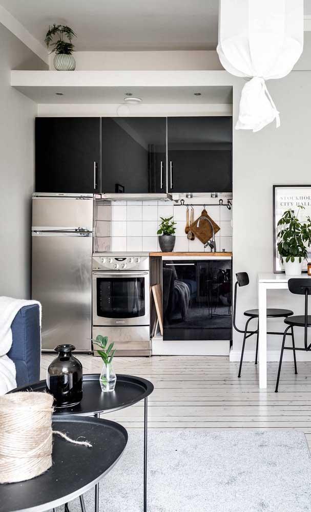 Cozinha compacta em preto e branco seguindo o estilo do restante do ambiente
