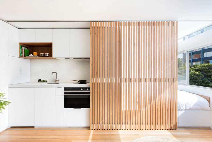 Olha essa ideia que máximo! O painel de madeira de correr cobre ora o quarto, ora a cozinha