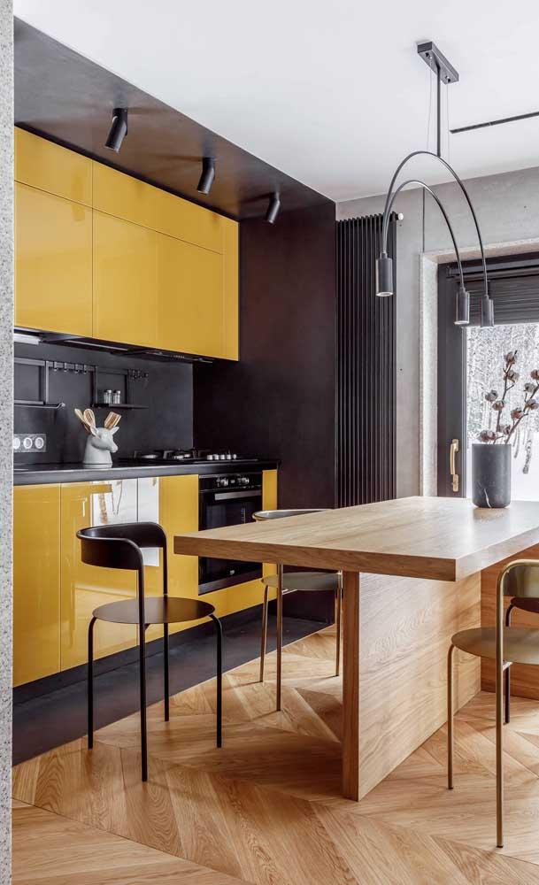 Cozinha compacta com móveis amarelos; repare no truque de demarcar o ambiente com uma faixa colorida que percorre o teto e as paredes