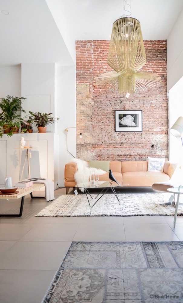 Essa sala super elegante trouxe a cor salmão em pequenos detalhes, como no sofá e até mesmo nas diferentes variações de cor dos tijolinhos aparentes