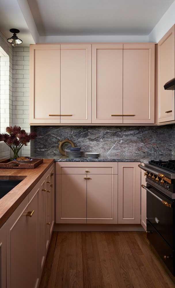 Uma cozinha elegante e sofisticada com armários na cor salmão, piso de madeira e bancada de mármore