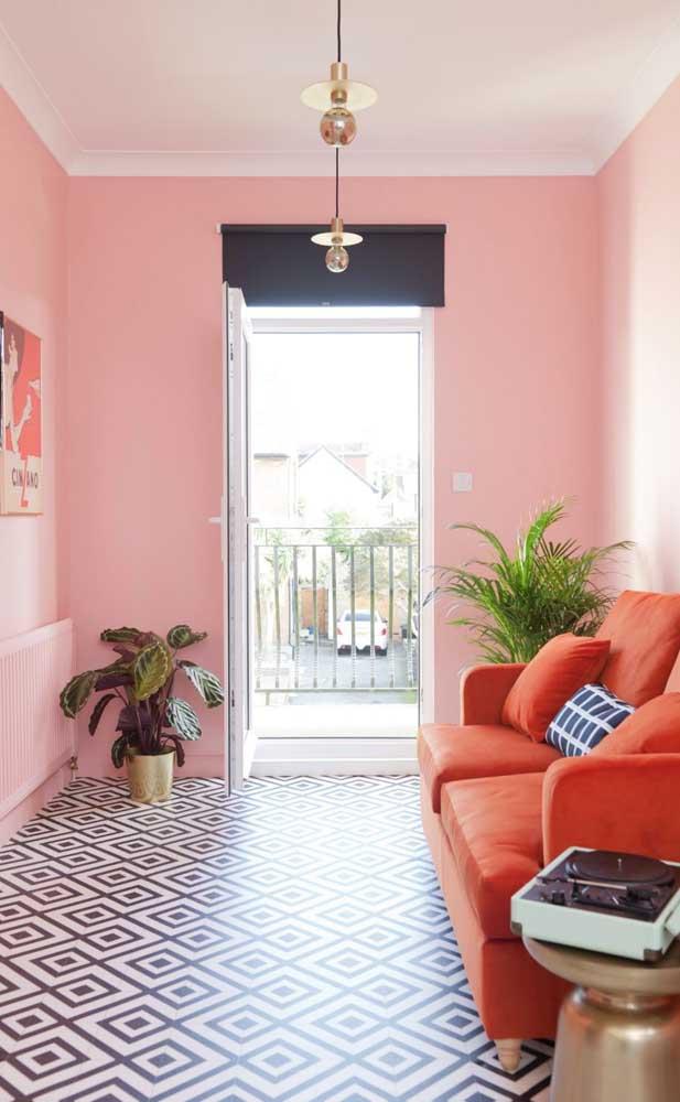 Inspire-se nessa combinação de cores análogas: parede salmão e sofá laranja; no chão, um piso preto e branco de arrancar suspiros
