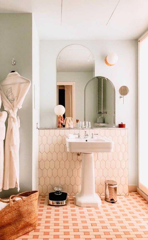 Nesse banheiro, a cor salmão entra nos detalhes do piso antigo que decora o chão