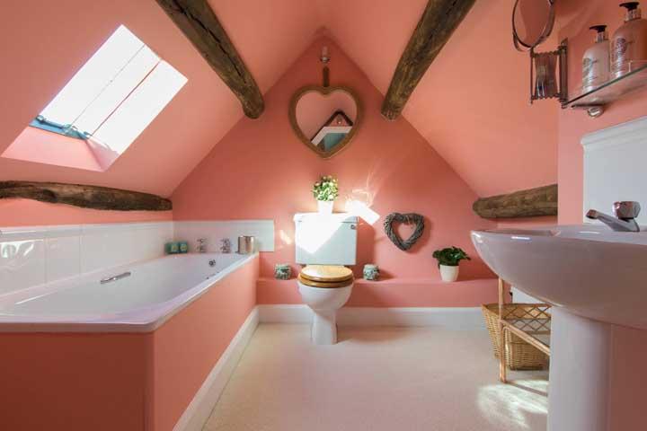 Romântico e acolhedor, esse banheiro traz o tom de salmão combinado a detalhes em madeira