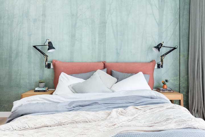 A floresta estampada no papel de parede atrás da cama ganhou a companhia das almofadas em tom de salmão