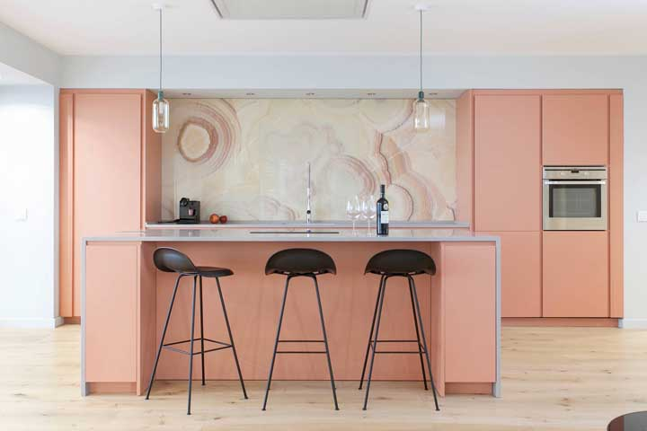 Sofisticação é a palavra que resume essa cozinha gourmet em tom salmão; repare que a pedra na bancada possui a mesma coloração