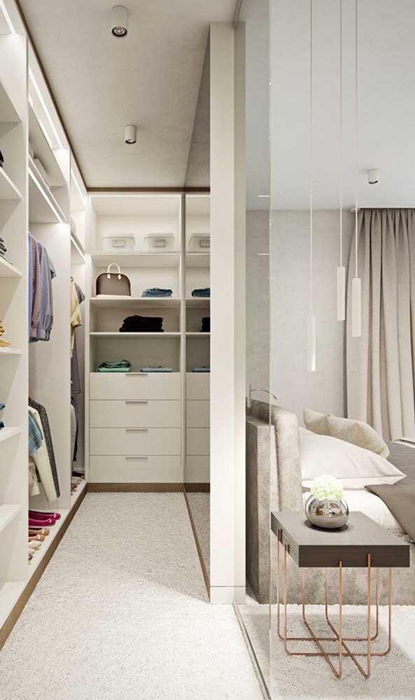 O destaque desse closet de casal é a divisória de gesso que abriga um espelho enorme em toda sua extensão