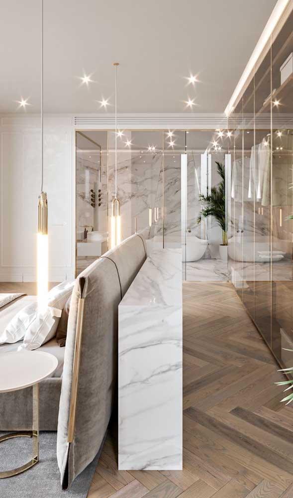 Para quem deseja um modelo de closet elegante, olha essa ideia: aqui, o closet foi integrado à suíte e dividido do quarto pelas paredes de vidro