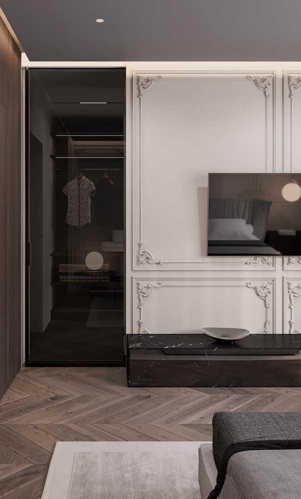 O clássico e o contemporâneo se unem nessa proposta de quarto com closet, onde a parede com boiserie divide harmoniosamente o espaço com a porta de vidro
