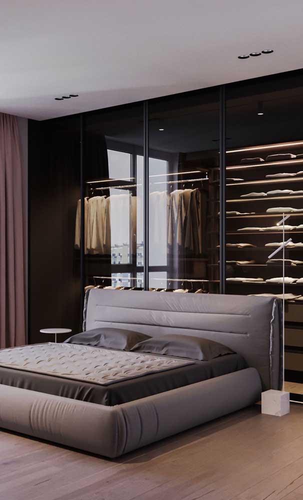 Prateleiras e araras à vista nesse closet com portas de vidro atrás da cama