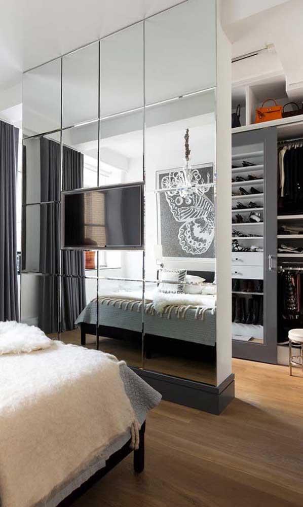 Olha que boa ideia de aproveitamento de espaço: a divisória do closet serviu também para apoiar a TV do quarto do casal